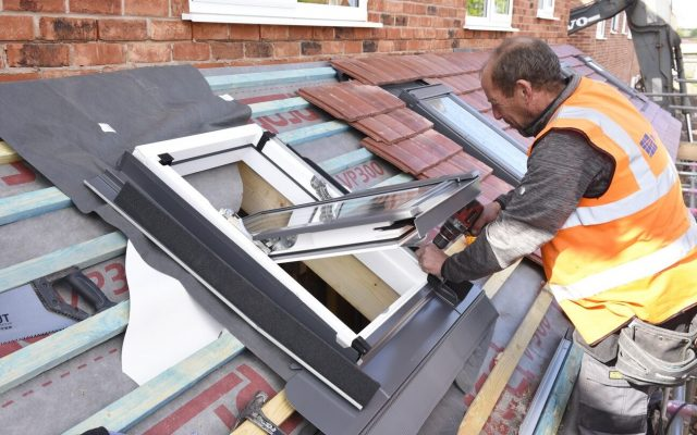 A house builder installing a window